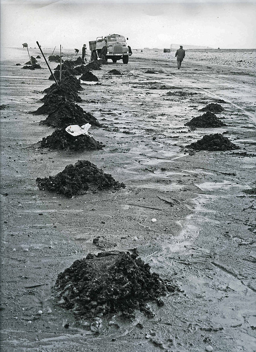 A black and white photograph of an old army vehicle and piles of coal on Hartlepool beach